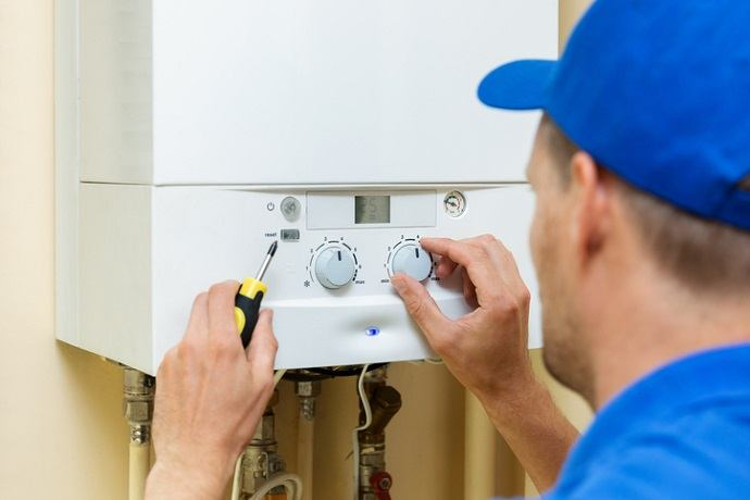 worker set up central gas heating boiler at home